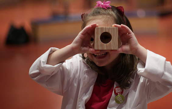 A girl looking through a wooden block with a hole in it.