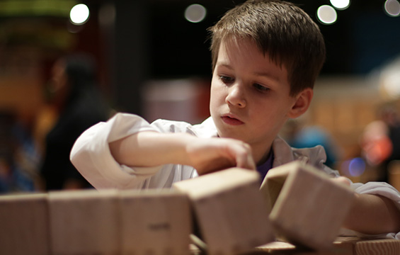 A young boy playing with wooden blocks at the Science Centre.