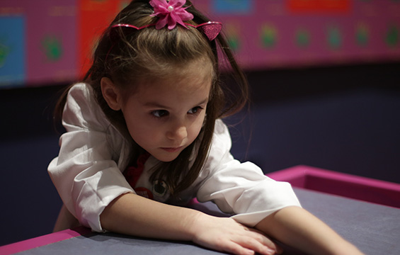 A young girl concentrates on learning at the Science Centre.