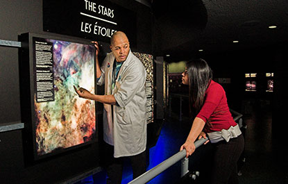 A host explains an exhibit to a visitor in the Space Hall.