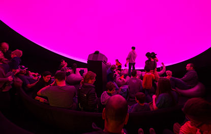 People prepare to enjoy a planetarium show.