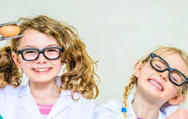 Two smiling young girls in glasses.
