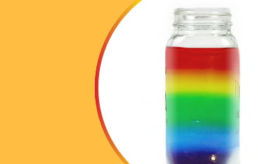 A jar filled with layers of rainbow coloured liquid.