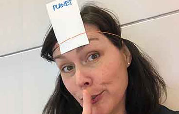 A woman with a piece of paper attached to her head that says Planet on it.
