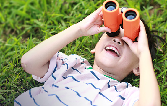 A young boy looks up at the sky with binoculars.