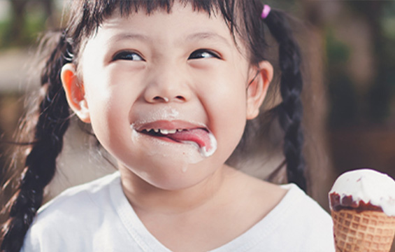A young girl holding an ice cream cone licks ice cream from her face.