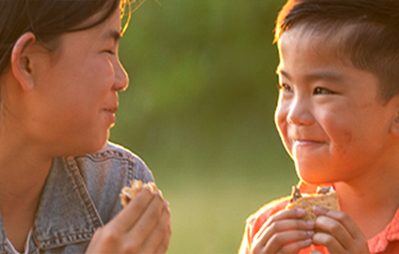 A woman and boy enjoy S'Mores together.