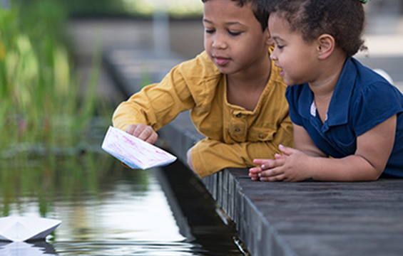 Two children launch paper boats into the water.
