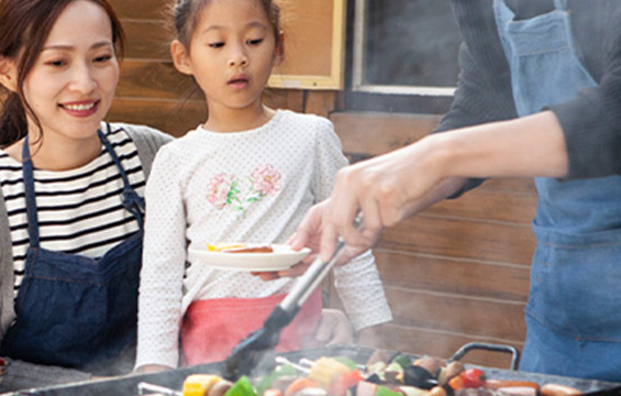 A woman and girl watch whole barbecue is being prepared.