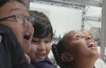 Three children with their mouths open in wonder at the Science Centre.