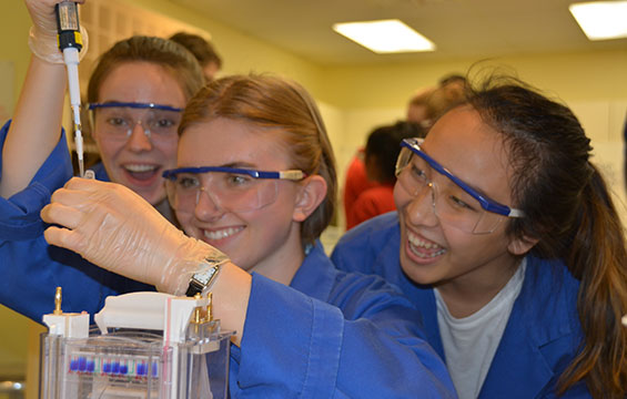 Three students in goggles and lab coats perform an experiment.