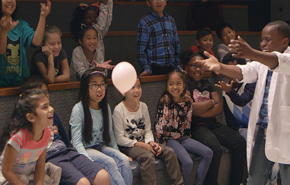 A group of students has fun learning about science with a balloon.