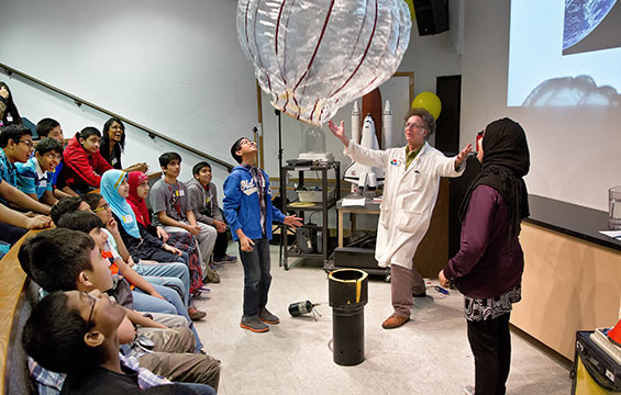 A class of students watches a Science Centre educator demonstrate with a large balloon.