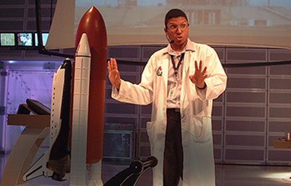 A host gives a presentation beside a large model of a space shuttle.