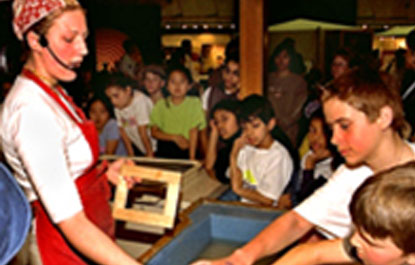 A host demonstrates paper making to a group of visitors.