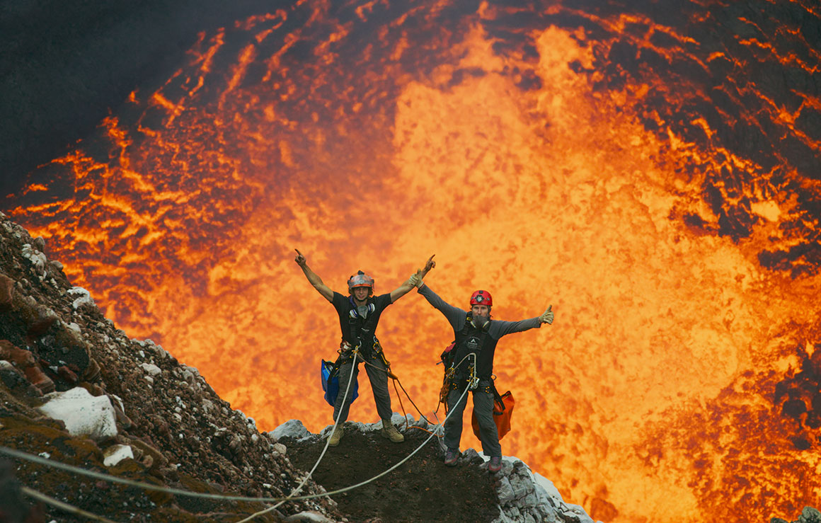 Two people raising their arms in front of a volcano cauldron.