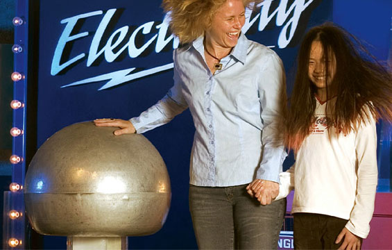 Two people touch the Van de Graaff generator making their hair stand on end.