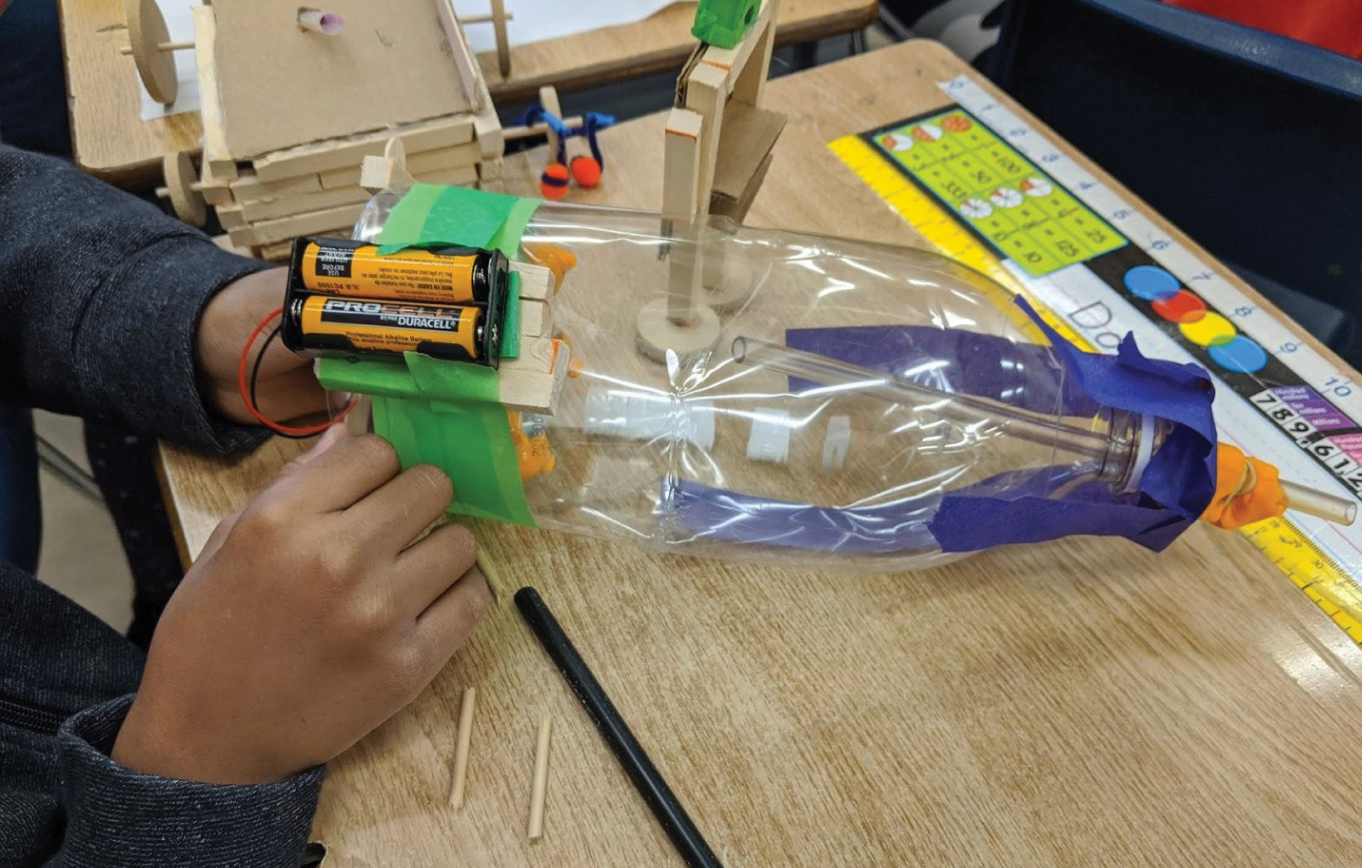 A student makes adjustments to the batteries attached to their engineering project