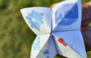 A hand folded paper toy with drawing of snow on it.