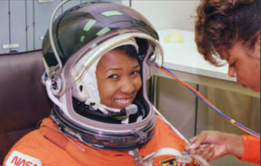 A woman helps an astronaut suit up.