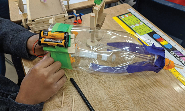 A student works on a home made science experiment involving batteries and a plastic bottle.
